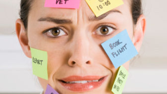 Businesswoman with sticky notes on face